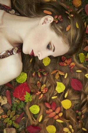 Fashion portrait of a beautiful young woman in autumn garden. Beauty autumn