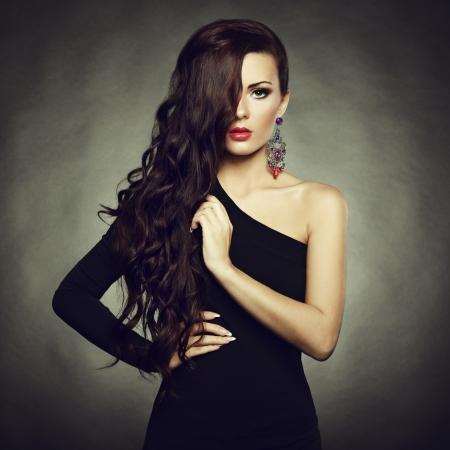 Retrato de mujer hermosa morena en vestido negro.