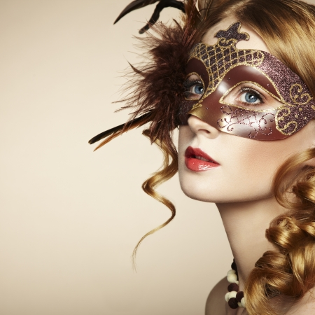 Beautiful young woman in brown mysterious venetian mask.