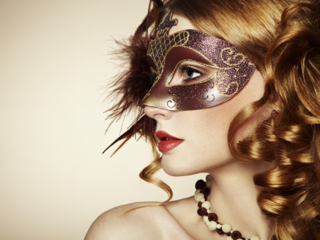 Beautiful young woman in brown mysterious venetian mask.  Stock Photo