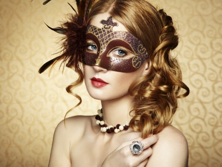 Beautiful young woman in brown mysterious venetian mask.   photo