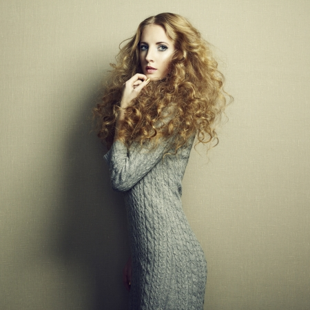 Portrait of beautiful woman in knitted dress. Fashion photo. Redhead girl
