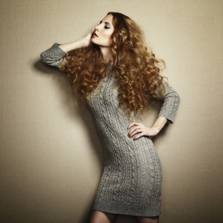 Portrait of beautiful woman in knitted dress. Redhead girl
