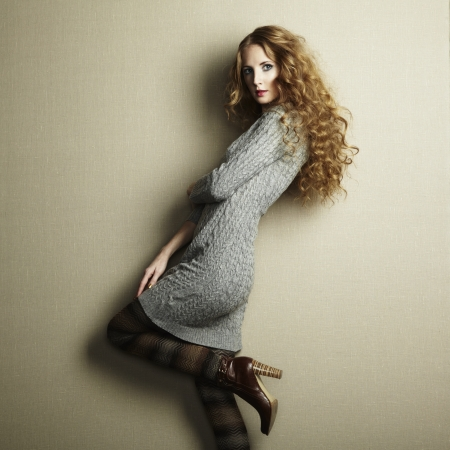 Portrait of beautiful woman in knitted dress. Redhead girl photo