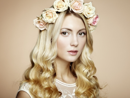 Portrait of a beautiful blonde woman with flowers in her hair. Fashion photo