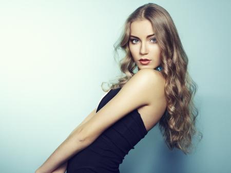 nude woman posing: Portrait of beautiful young blonde girl in black dress. Fashion photo