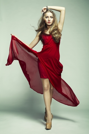 Fashion photo of young magnificent woman in red dress. Studio photo photo