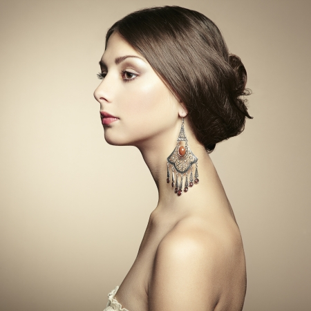 Portrait of beautiful young woman with earring. Fashion photo photo