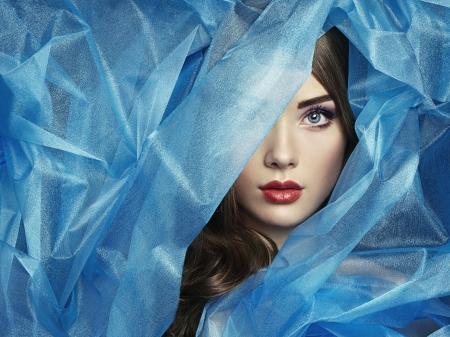 Fashion photo of beautiful women under blue veil. Beauty portrait