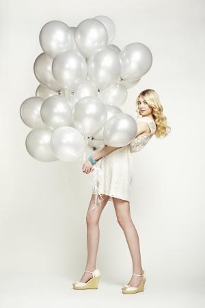 Fashion photo of beautiful woman with balloons. Girl posing. Studio photo photo