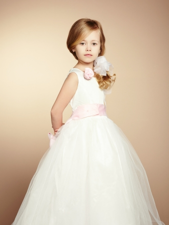 comb hair: Portrait of little girl in luxurious dress. Fashion photo