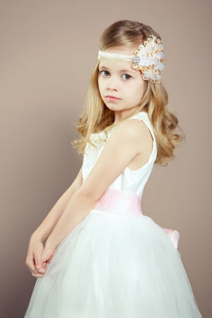 seductress: Portrait of little girl in luxurious dress. Fashion photo