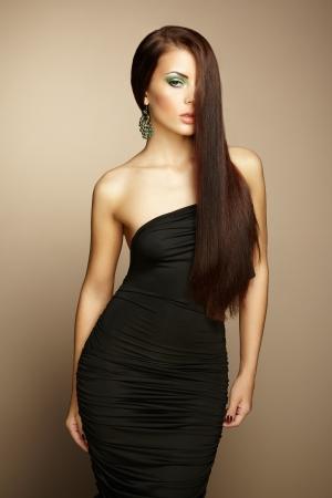 Portrait of beautiful brunette woman in black dress. Fashion photo photo