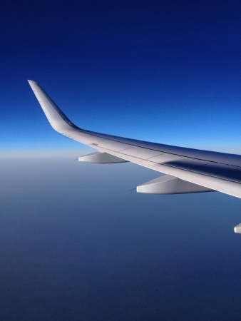 Airplane wing on the sky background