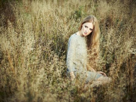 Portrait of beautiful woman on autumn field. Fashion photo photo