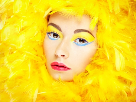 Portrait of beautiful girl in yellow feathers photo