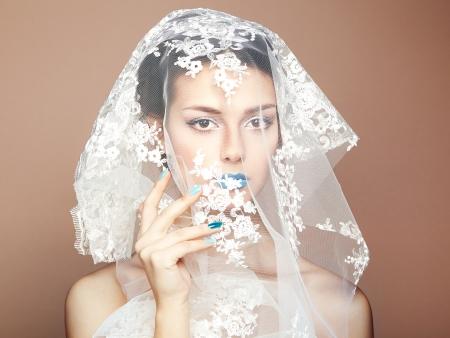 Fashion photo of beautiful women under white veil photo