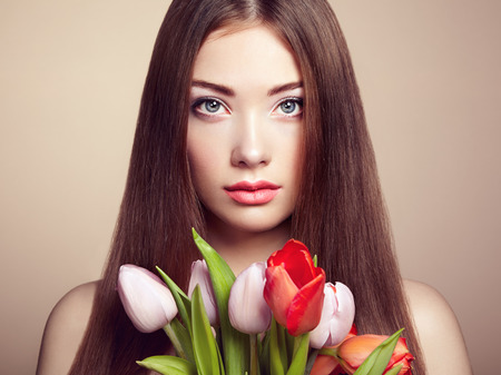 Portrait of beautiful dark-haired woman with flowers. Fashion photo photo