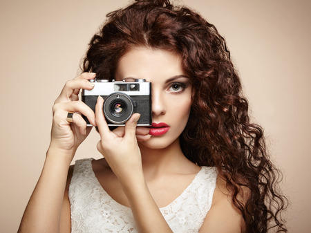 Portrait of beautiful woman with the camera. Girl photographer. Fashion photo photo
