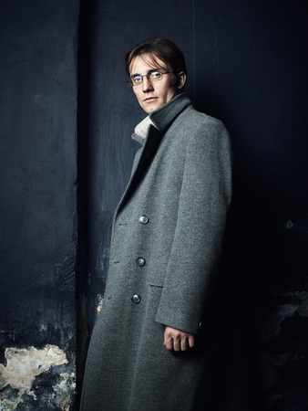 greatcoat: Artistic dark portrait of the young beautiful man in a gray coat  Close up
