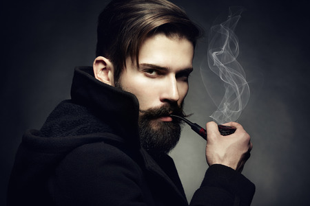Artistic dark portrait of the young beautiful man  The young man smokes a tube  Close up