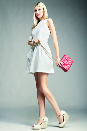 Fashion photo of young magnificent woman. Girl with handbag. Girl posing photo