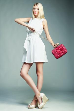 Fashion photo of young magnificent woman. Girl with handbag. Girl posing photo