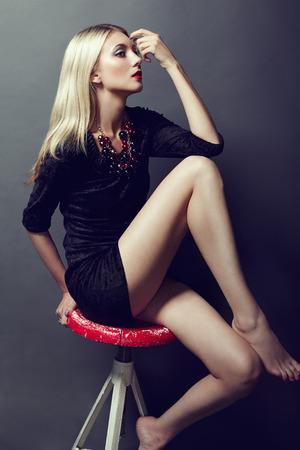 seductive women: Photo of beautiful blonde woman in black dress. Fashion photo Stock Photo
