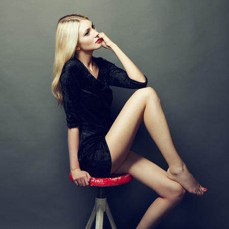 leggings: Photo of beautiful blonde woman in black dress. Fashion photo Stock Photo