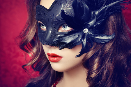 Beautiful young woman in black mysterious  Venetian mask  Fashion photo