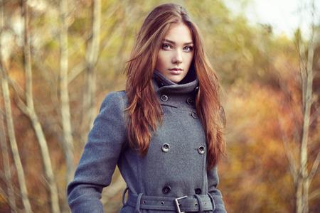 al aire libre: Retrato de la mujer hermosa joven en el abrigo de otoño. Foto de moda