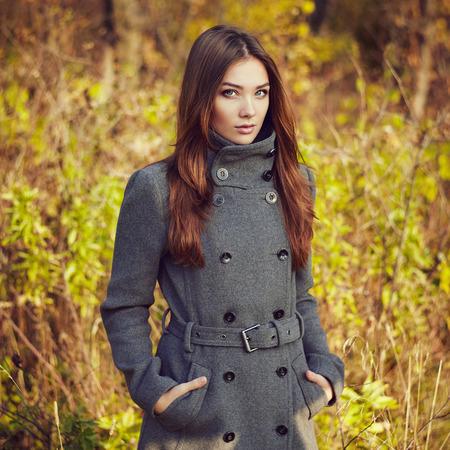 pelirrojas: Retrato de la mujer hermosa joven en el abrigo de otoño. Foto de moda