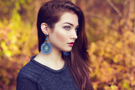jewelry: Portrait of young beautiful woman in autumn park. Beauty. Fashion photo