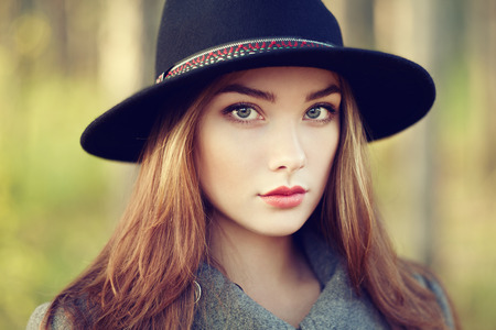 Portrait of young beautiful woman in autumn coat. Girl in hat. Fashion photo photo