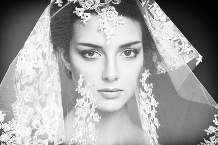 Fashion photo of beautiful women under white veil. Beauty portrait. Black and white photo