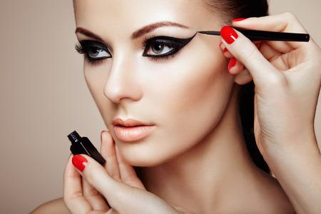 Makeup artist applies eye shadow. Beautiful woman face. Perfect makeup Stock Photo