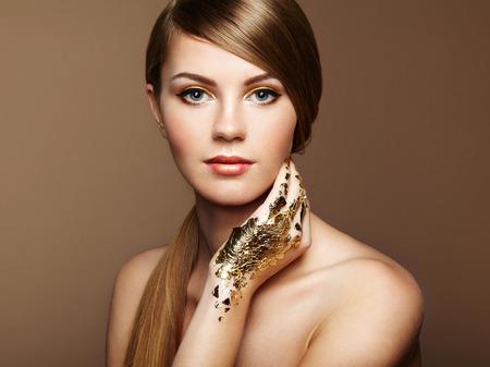 naked young woman: Portrait de femme magique en or. Jeune fille blonde. Maquillage parfait. photo de mode