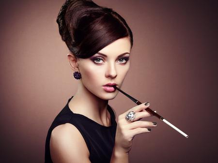 modelos desnudas: Retrato de la hermosa mujer sensual con elegante estilo de peinado. Mujer con maquillaje perfecto cigarrillo. Foto de moda Foto de archivo