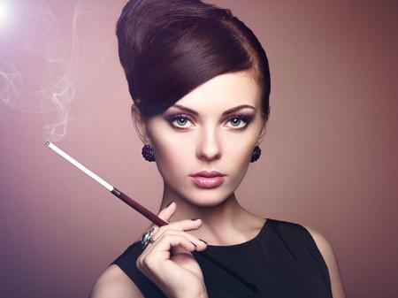 chica fumando: Retrato de hermosa mujer sensual con elegante peinado. Mujer con maquillaje perfecto cigarrillo. Foto de moda