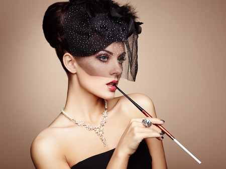 sexy girl smoking: Portrait of beautiful sensual woman with elegant hairstyle.  Woman with cigarette Perfect makeup. Fashion photo