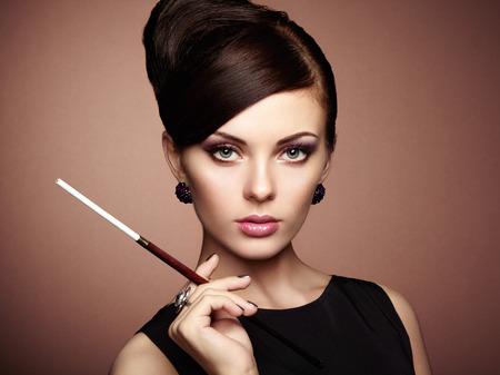 エレガントなヘアスタイルで美しい官能的な女性の肖像画。タバコの完璧なメイクを持つ女性。ファッション写真 写真素材