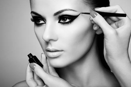 메이크업 아티스트는 아이섀도를 적용합니다. 아름 다운 여자의 얼굴. 완벽한 메이크업. 흑백 사진