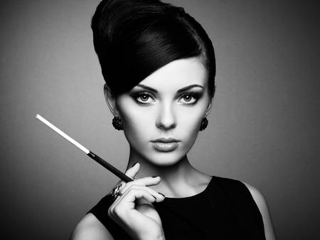 우아한 헤어 스타일을 가진 아름 다운 관능적 인 여자의 초상화입니다. 담배 완벽한 메이크업을 가진 여자입니다. 패션 사진. 흑백 사진