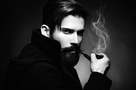 greatcoat: Artistic dark portrait of the young beautiful man. The young man smokes a tube. Close up. Black and white photo Stock Photo