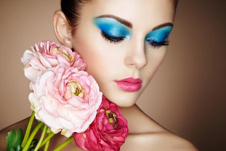 花と美しい若い女性の肖像画。完璧なメイク。完璧な肌。ファッション写真