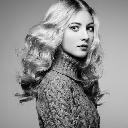 ragazze bionde: Foto di moda della bella donna in maglione. Acconciatura riccia. Trucco. In bianco e nero Archivio Fotografico