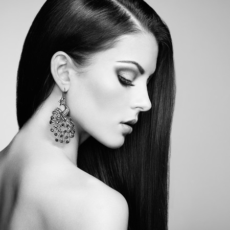 nude brunette: Portrait of beautiful brunette woman with earring. Perfect makeup. Fashion photo. Black and White