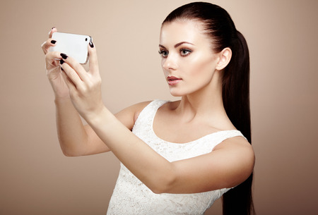 photographing: Beautiful young woman taking selfie. Girl photographing herself with phone. Beauty fashion. Eyelashes. Cosmetic Eyeshadow
