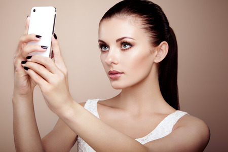 Beautiful young woman taking selfie. Girl photographing herself with phone. Beauty fashion. Eyelashes. Cosmetic Eyeshadow