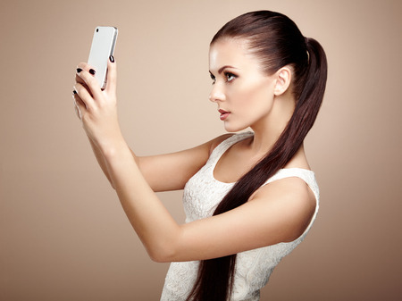ladylike: Beautiful young woman taking selfie. Girl photographing herself with phone. Beauty fashion. Eyelashes. Cosmetic Eyeshadow